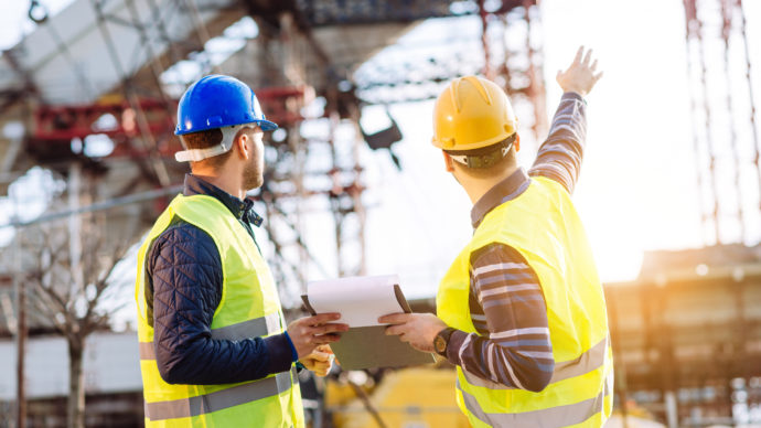 Two professionals on a construction site planning ahead