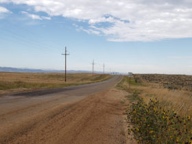 Picture of East Antelope Road with fields beside it and blue sky above