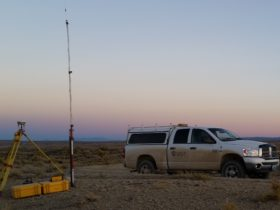 Land surveying equipment next to a WLC truck at sunset